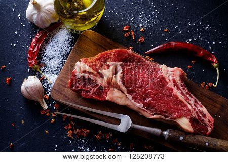 Raw meat steak entrecote on the plate with spice on the dark table