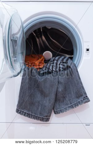 A close up of a washing machine loaded with clothes. Household appliance.