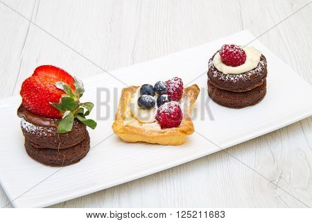 a long dish with trio of cakes with fruit
