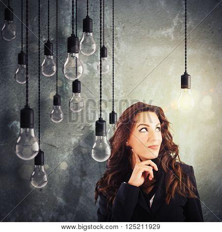 Woman with lit lightbulb among unlit bulbs
