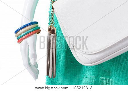 Colorful bracelets on female mannequin. Set of woman's bright bracelets. White purse and bijouterie. Sale of colorful accessories.