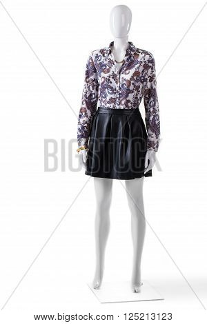 Mannequin in skirt and shirt. Woman's floral shirt with skirt. Trendy evening outfit with jewelry. Expensive clothes from new catalog.