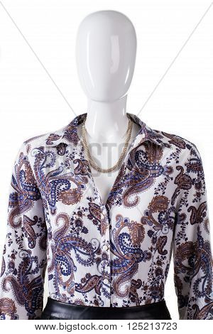 Necklace and shirt on mannequin. Woman's unbuttoned shirt with necklace. Floral pattern garment and jewelry. Luxury look for young ladies.