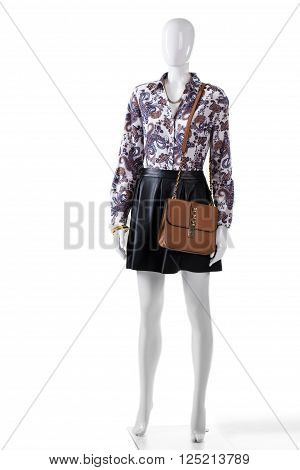Mannequin wearing skirt and purse. Dark skirt with leather handbag. Girl's floral shirt and bag. Evening outfit with brown purse.