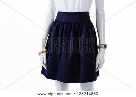 Dark navy skirt on mannequin. Navy skirt and wrist accessories. Navy cotton skirt with folds. Girl's high-quality cotton garment.