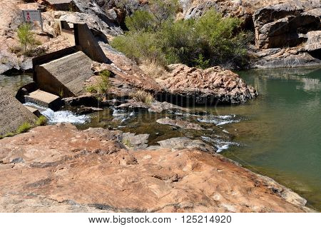 Small dam at Serpentine Falls with granite rock and natural green rock pools in Serpentine, Western Australia.