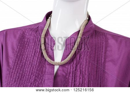 Purple shirt with silver necklace. Stylish accessory on mannequin's neck. Lady's exclusive jewelry. Colorful garment and expensive necklace.