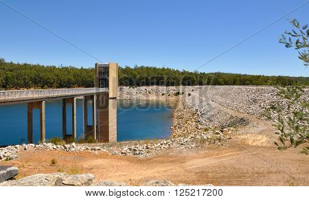 Views of Serpentine Dam with the Serpentine River basin, and elevated walkway and partial bridge bordered by a lush green forest under a clear blue sky in Serpentine, Western Australia.