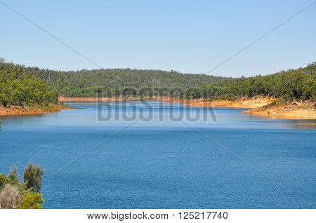 Tranquil scenic view overlooking the Serpentine River, bordered with a lush green forest, under a blue sky in Serpentine, Western Australia.