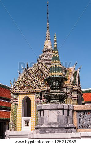 Small temple with spires against a dark blue sky at Grand Palace, Thailand