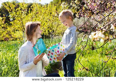 young beautiful mother and her adorable son sitting together in the park at spring time celebrating mother's day, boy giving her mother present, mother opening it and looking happy