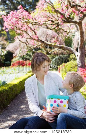 young beautiful mother and her adorable son sitting together in the park at spring time celebrating mother's day boy giving her mother present and looking at each other