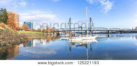 luxury yacht on tranquil sea and steel bridge in blue sky in portland