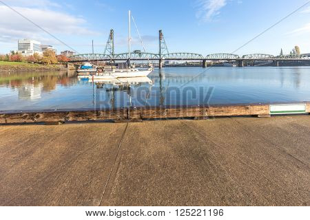 empty old concrete floor with luxury yacht and steel bridge in blue sky in portland