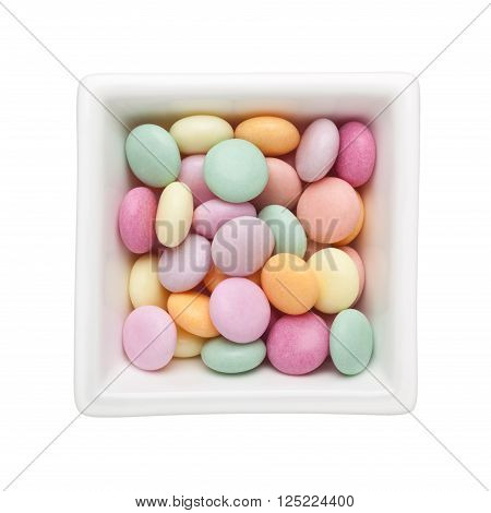 Colorful candy in a square bowl isolated on white background