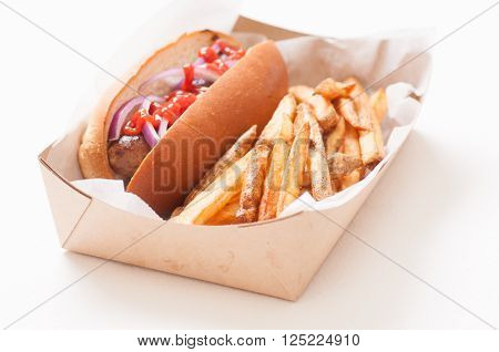 bratwurst sausage on a bun with fresnch fries ketchup and onions