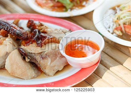 Grilled chicken and chicken sauce on wood table it's name KAI YANG in Thailand