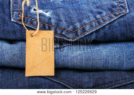 stack jeans closeup with blank cardboard price tag for your text