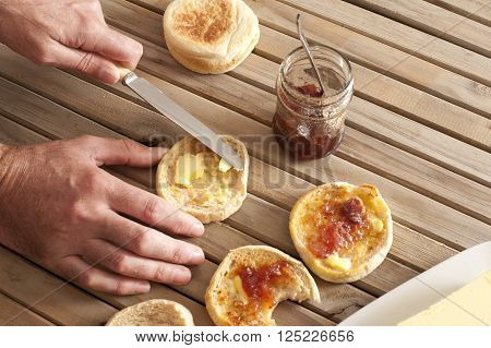 Hands spreading butter and strawberry marmalade on toasted english muffins with a knife