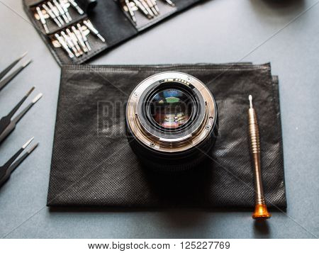 Photo camera lens repair and expertise set. Maintenance support of photographic 50 1.4 photo camera lens. Optical dslr lens service with dust