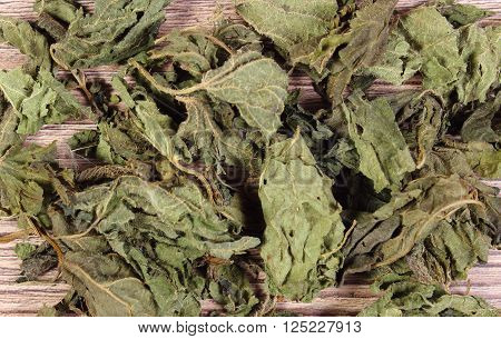 Heap of healthy dried nettle on wooden table, concept for healthy nutrition and herbalism