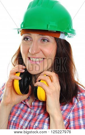 Smiling female construction worker wearing green helmet and protective headphones safety at work and ear protection. Isolated on white background