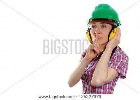 Female construction worker wearing green helmet and protective headphones, showing silence sign, safety at work and ear protection, copy space for text. White background