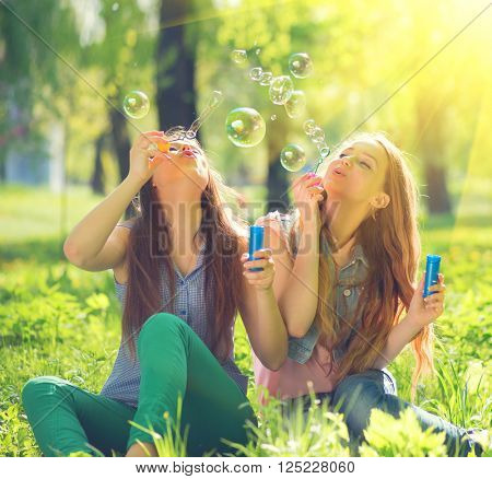 Beauty teen girls having fun outdoors. Beautiful joyful teenagers laughing and blowing soap bubbles in spring park. Girlfriends outdoor. Friendship