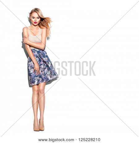 Fashion model Girl full length portrait dressed in short skirt and beige top, beige high-heeled shoes. Blowing hair. Beautiful young woman posing in studio