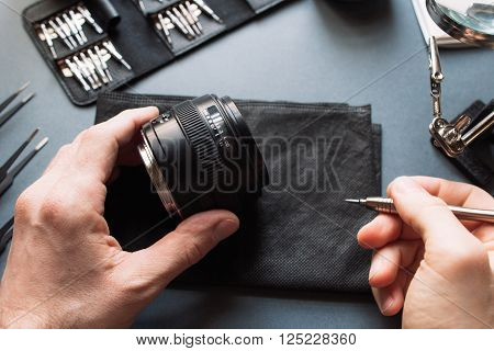 Engineer repair photo camera lens set. Expertise and maintenance support of photographic 50 1.4 photo camera lens. Pov to workplace and engineer's hands.