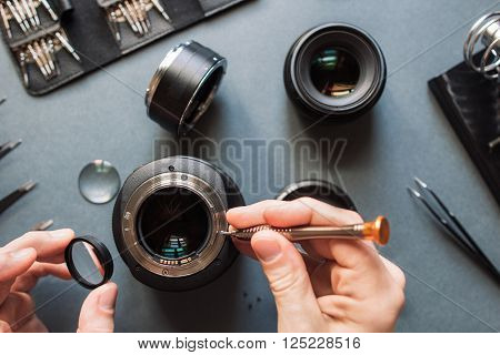 Photo camera lens repair set. Technician engineer check optics alignment and maintenance support of broken photographic 85 1.2 photo camera lens part. Pov to workplace and engineer's hands.