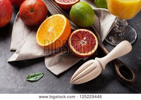 Fresh ripe citruses. Lemons, limes and oranges on dark stone background