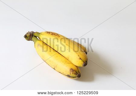 Yellow ripe banana with brown spots on white isolated background