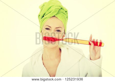 Beautiful woman with oversized toothbrush.