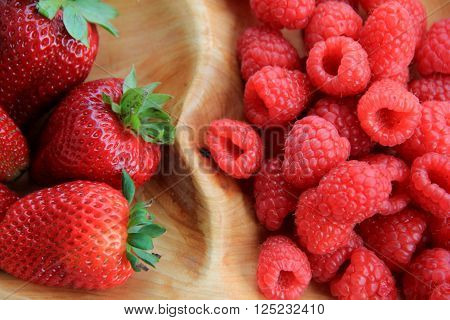 Wood tray holding fresh picked strawberries and raspberries