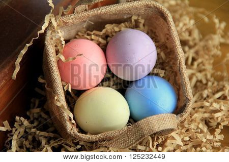 Four colorful chalk eggs in hand crafted basket makes cute Springtime decoration in home.