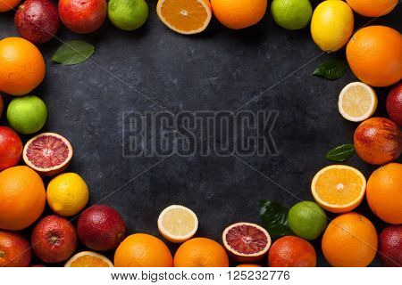Fresh ripe citruses frame. Lemons, limes and oranges on dark stone background. Top view with copy space