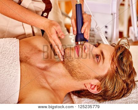 Relaxed young man luxuriating on electroporation  facial therapy at beauty salon.