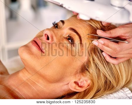 Woman middle-aged in spa salon with young beautician. Tweezing eyebrow by beautician. Woman in a retracting eyebrows spa.