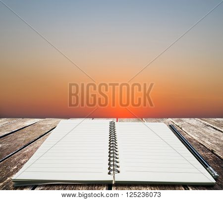 Opened notebook with pencil, selective focus on wooden panels at the beach with sunset view