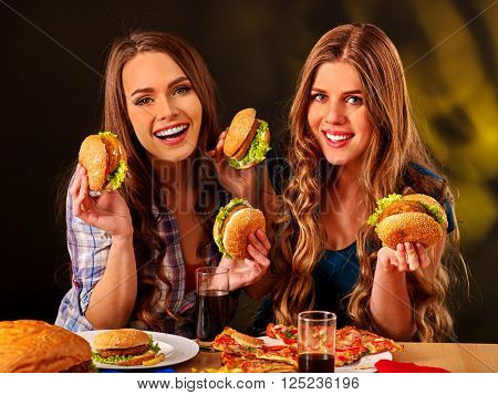 Two happy girls bite burger with two sides. Fastfood concept.