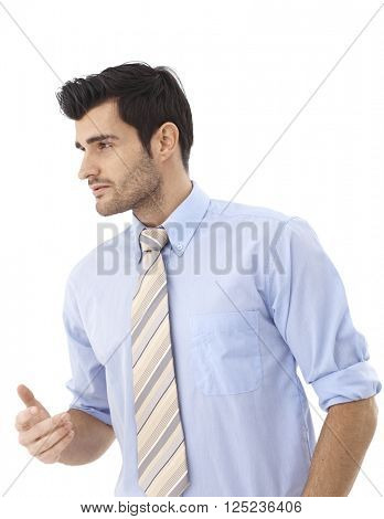 Young businessman turning right, gesturing over white background.