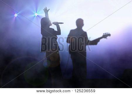 Women on stage singing with guitarist under spotlight