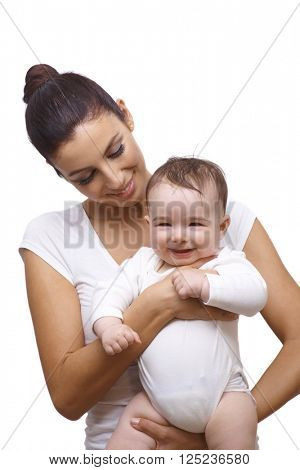Portrait of young mother holding baby boy in arm both smiling.