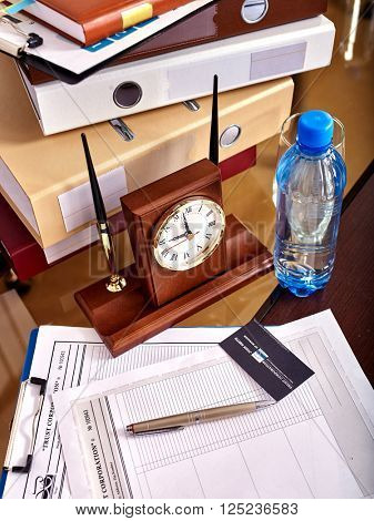 Business set on the table. Business interior on table with clock and leather chair in office.