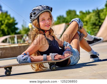 Teen girl in helmet sitting on his skateboard outdoor. Fall on person . Girl lying on a skateboard in a skate park.