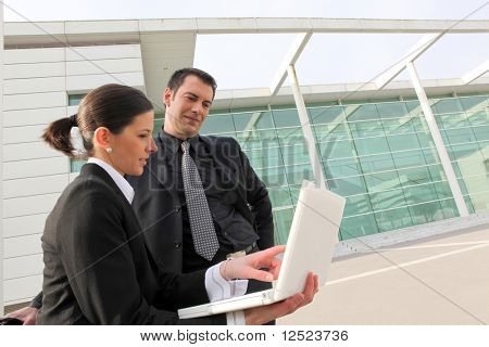 Business people in front of modern building with laptop