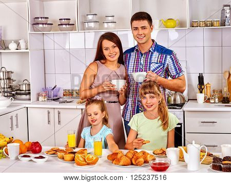 Parents prepare  breakfast for child. Big family with two kids having breakfast in the white kitchen. Happy family and children.