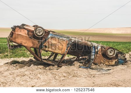Abandoned rusty burnt car wreck.