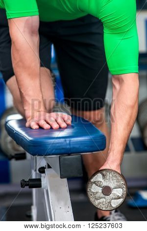 Man working his arms with dumbbells at gym. Close up of hands. Man shakes hands in the gym. Man working his arms at gym.